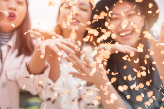 Blurred asian friends having fun throwing confetti at party outdoor - Young trendy people enjoying fest event - Hangout, friendship, trends and youth concept - Defocused photo