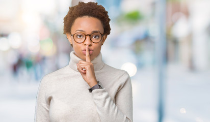 Young beautiful african american woman wearing glasses over isolated background asking to be quiet with finger on lips. Silence and secret concept.