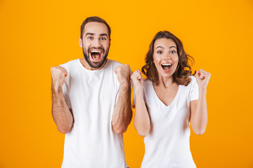 Image of ecstatic people man and woman in basic clothing laughing, while standing together isolated over yellow background