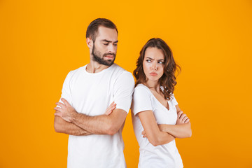 Photo of resented man and woman in quarrel standing back to back with arms folded, isolated over yellow background