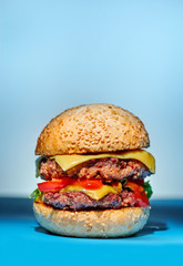 Hamburger with beef, cheese and vegetables on blue background