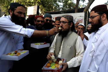 People distribute sweets as they celebrate after Pakistan shot down two Indian military aircrafts, in Karachi