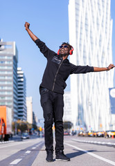 Front view of a black man wearing casual clothes and sunglasses standing in the street while using headphones to listen music in sunny day