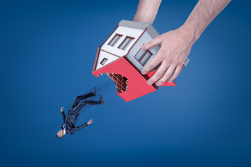 Close-up of man's hands holding house with hole in roof upside down and dropping out little businessman.