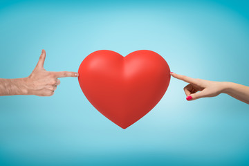 Woman's hand on the right and man's hand doing finger gun on the left touching a big red Valentine heart in the middle on blue background.