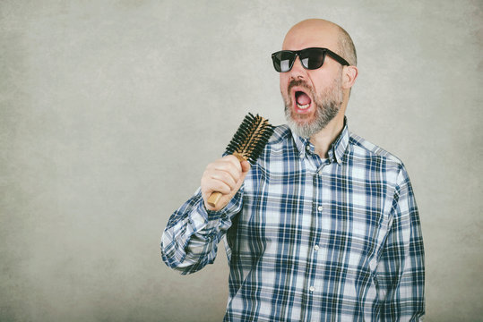 bald man with sunglasses singing a hair brush