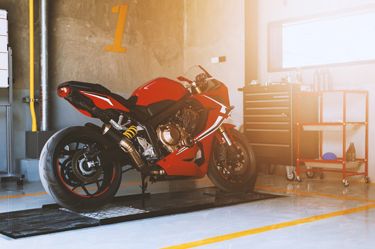 closeup sport motorcycle in repair station and body shop with soft-focus and over light in the background