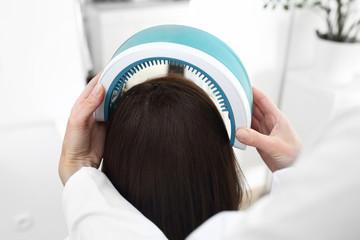 Laserowa terapia skóry głowy i włosów. Kobieta z cienkimi  i słabymi włosami na zabiegu w...