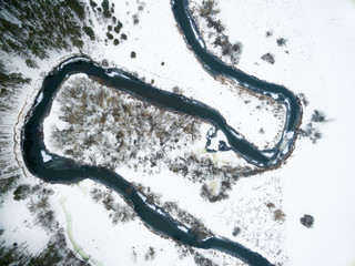 Winter landscape on the river with a forest among snow with a bird's-eye view. Drone view photo from the drone on a cloudy day. Aerial top view beautiful snowy landscape