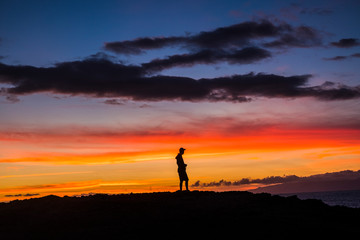Man standing outdoor looking and enjoying the romantic sunset - feeling the nature and happiness for free lifestyle - people and outdoor show with coloured clouds in the dawn time