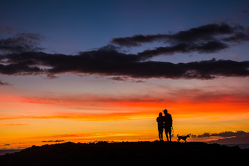Romantic couple wioth dog enjoying and looking the sunset with red and orange coloured clouds in the sky - wanderlust and travel concept for happy people - dawn and colors background concept