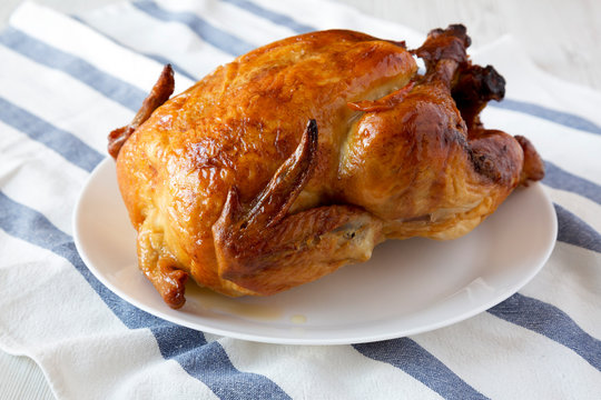 Homemade rotisserie chicken on white plate, side view. Close-up.