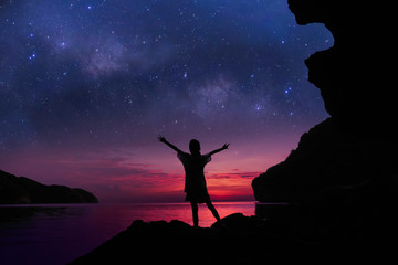 The girl standing on the rocks near the beach with beautiful million stars galaxy