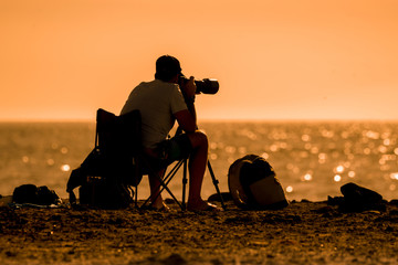 Silhouette of a photographer at the sunset sitting near the sea. Man with photo camera taking pictures at the beach. Ocean in the background Orange sky and waves. Summer vacation evening landscape