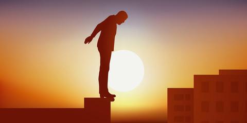 Concept de la dépression et du désespoir avec un homme debout sur le bord d'un toit d'immeuble qui est prêt à se suicider.