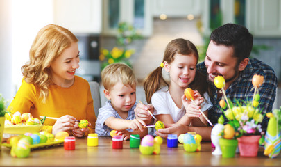 Happy easter! family mother, father and children paint eggs for holiday.