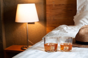 Two glasses of whiskey with ice on bed and lighting lamp in background