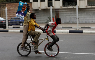 Boy holding a picture of Nigeria's President Muhammadu Buhari rides a bicycle with others as they celebrate in Kano