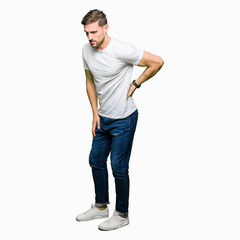 Handsome man wearing casual white t-shirt Suffering of backache, touching back with hand, muscular pain