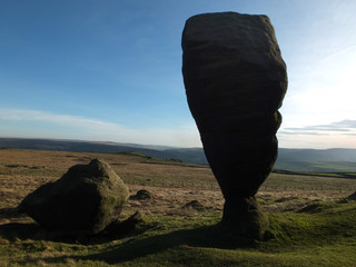 the great bridestone a large natural monolithic rock formation on west yorkshire moorland near todmorden in shadow against a bright blue sky