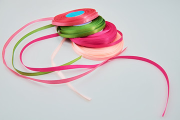 Four colored ribbons on the reels. Gray background.