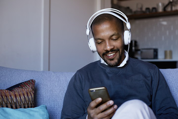 Attractive African American man with headphones listening to music on his phone. Concept of relaxation