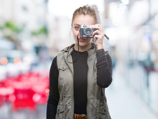 Young blonde woman taking pictures using vintage camera over isolated background with a confident expression on smart face thinking serious