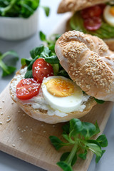 Bagel sandwiches with cream cheese, avocado, tomatoes, egg and greens on gray wooden background. Selective focus. Healthy eating or vegetarian food concept