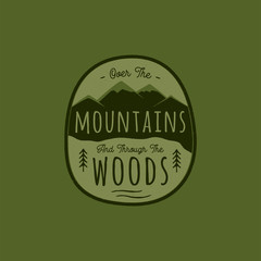 Hand drawn adventure logo with mountain, pine trees forest and quote - Over the Mountains and through the woods. Old style camp outdoors emblem in retro style. Stock vector illustration