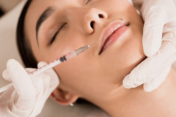 close up of beautiful asian woman getting beauty injection at clinic