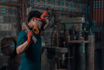 Mechanical engineer taking a break and wiping sweat off his forehead while resting a pipe wrench on his shoulder during his work shift