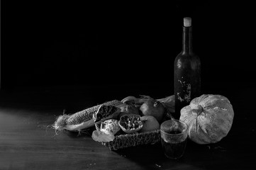otten and withered fruits in old basket on brown wooden table and old juice old bottle which has dim light