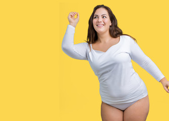 Beautiful plus size young overwight woman wearing white underwear over isolated background Dancing happy and cheerful, smiling moving casual and confident listening to music