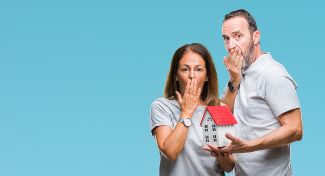 Middle age hispanic casual couple buying new house over isolated background cover mouth with hand shocked with shame for mistake, expression of fear, scared in silence, secret concept