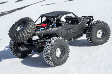 Radio controlled car models: a small black buggy toy with dirty splashes stands in the snow.