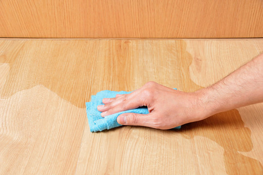 Man hand wiping wooden laminate parquet floor with blue sponge