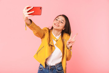 Girl posing isolated over pink background take selfie by mobile phone.