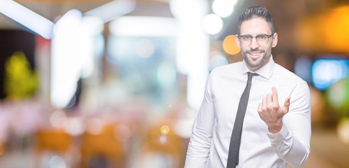 Young handsome business man wearing glasses over isolated background Beckoning come here gesture with hand inviting happy and smiling