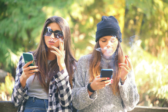 two girls smoking cigarettes and using smart phones. concept of addiction to smoking and smart phone dependency..