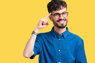 Young handsome man wearing glasses over isolated background Smiling pointing to head with one finger, great idea or thought, good memory