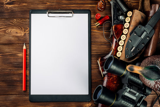 Blank clipboard and pen with hunting equipment on the wooden background.