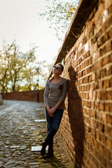 Young beautiful caucasian woman in sunglasses and casual outfit lean on the brick wall and looks aside. Spring day