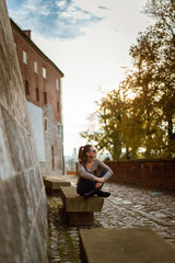 Young beautiful caucasian woman in sunglasses and casual outfit sitting on the concrete bench and dreaming. Spring day