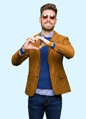 Young handsome elegant man wearing sunglasses smiling in love showing heart symbol and shape with hands. Romantic concept.