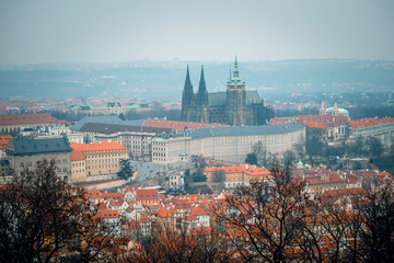 Top view of beautiful city of Prague, buildings with red roofs and Prague castle. Czech Republic. Gloomy day