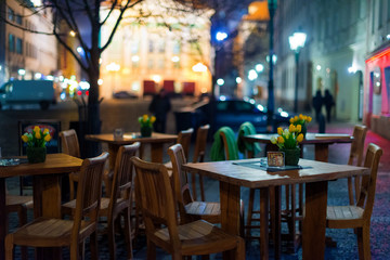 Outdoor restaurant with wooden tables on the European square. Empty outdoor Cafe. Blurred background.