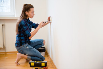 Young brunette woman in plaid shirt repairs an electric socket with a screwdriver. Installingnew socket into the wall