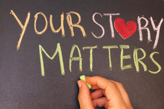 your story matters phrase handwritten on blackboard with heart symbol instead of O, hand holding green chalk