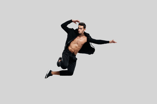 Handsome young dancer of street dancing dressed in black pants and a sweatshirt on a naked torso jumps on a white background
