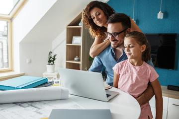 Middle age businessman working at home.Wife and daughter  stands beside and support him.